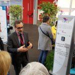 Stéphan Maret, directeur de la communication et du mécénat du CHU de Poitiers et trésorier du fonds Aliénor, présente aux officiels, lors de l'inauguration du salon, la borne de dons, aux côtés d'Amaury de Préville, directeur régional d'AG2R La Mondiale.
